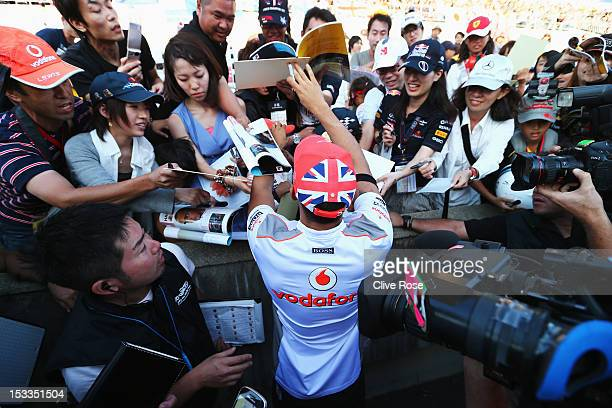 Lewis Hamilton of Great Britain and McLaren signs autographs for fans during previews for the Japanese Formula One Grand Prix at the Suzuka Circuit...