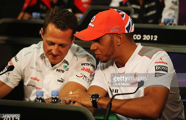 Lewis Hamilton of Great Britain and McLaren talks with Michael Schumacher of Germany and Mercedes GP at the drivers press conference during previews...
