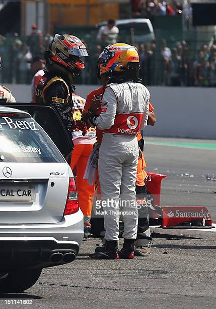 Lewis Hamilton of Great Britain and McLaren talks with Romain Grosjean of France and Lotus after they crash out at the first corner at the start of...