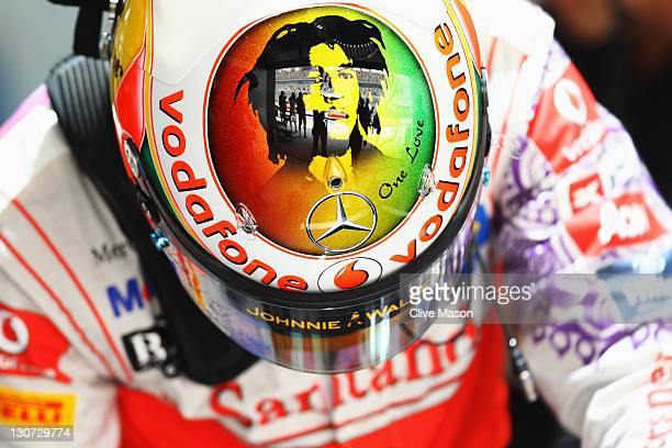 Lewis Hamilton of Great Britain and McLaren wears a specially designed helmet with tribute to the late reggae musician Bob Marley as he prepares to...