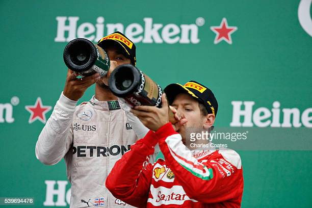 Lewis Hamilton of Great Britain and Merccedes GP celebrates his win on the podium with Sebastian Vettel of Germany and Ferrariduring the Canadian...