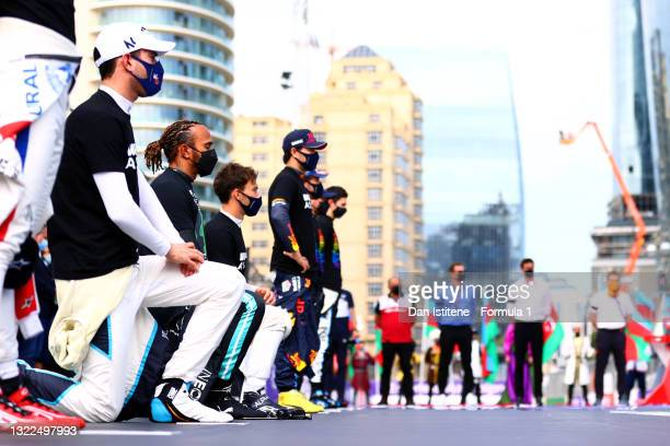 Lewis Hamilton of Great Britain and Mercedes AMG Petronas takes the knee next to his fellow drivers on the grid as they observe a moment in support...