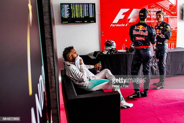 Lewis Hamilton of Great Britain and Mercedes contemplates his win before going to the podium along with Daniel Ricciardo of Australia and Max...