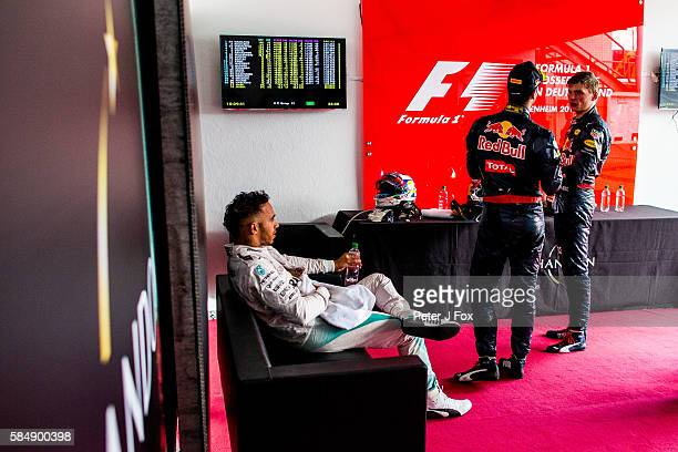 Lewis Hamilton of Great Britain and Mercedes contemplates his win before going to the podium with Daniel Ricciardo of Australia and Max Verstappen of...