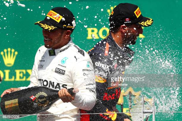 Lewis Hamilton of Great Britain and Mercedes GP and Daniel Ricciardo of Australia and Red Bull Racing celebrate on the podium after the Canadian...
