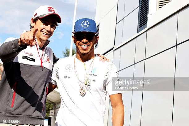 Lewis Hamilton of Great Britain and Mercedes GP and Esteban Gutierrez of Mexico and Haas F1 joke around in the paddock during practice for the...