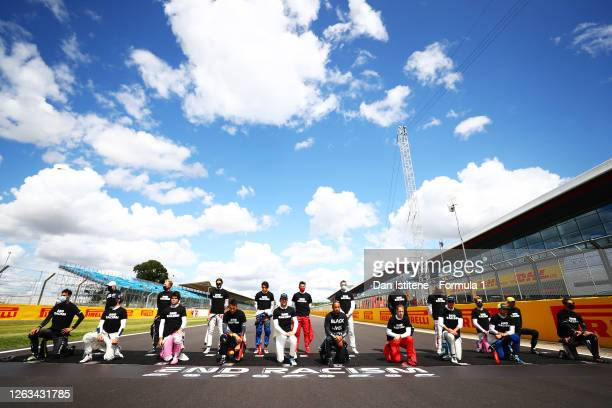 Lewis Hamilton of Great Britain and Mercedes GP and his fellow F1 drivers stand at the front of the grid in support of the movement to end racism...