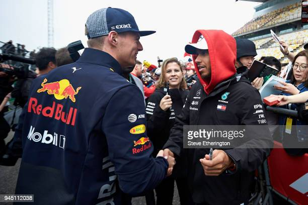 Lewis Hamilton of Great Britain and Mercedes GP and Max Verstappen of Netherlands and Red Bull Racing shake hands in the Paddock during previews...