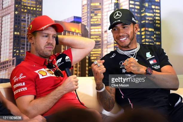 Lewis Hamilton of Great Britain and Mercedes GP and Sebastian Vettel of Germany and Ferrari react during a press conference during previews ahead of...