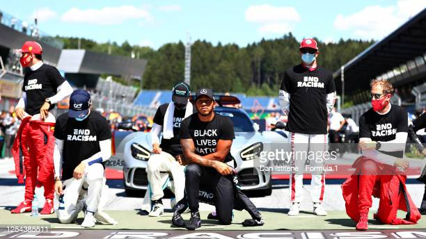 Lewis Hamilton of Great Britain and Mercedes GP and Sebastian Vettel of Germany and Ferrari takes a knee on the grid before the Formula One Grand...