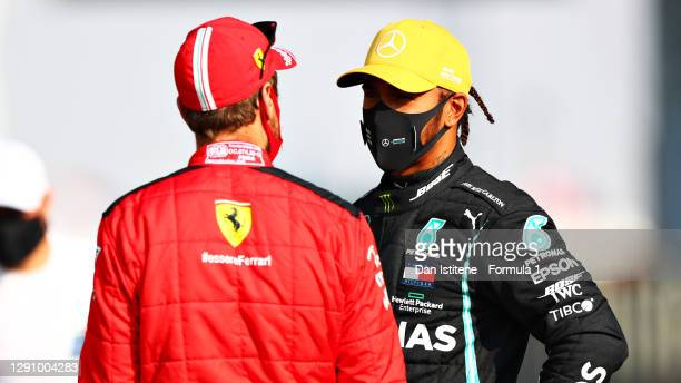 Lewis Hamilton of Great Britain and Mercedes GP and Sebastian Vettel of Germany and Ferrari talk on the grid prior to the F1 Grand Prix of Abu Dhabi...