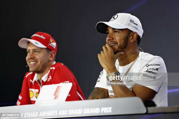 Lewis Hamilton of Great Britain and Mercedes GP and Sebastian Vettel of Germany and Ferrari look on in the Drivers Press Conference during previews...