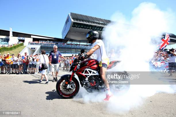 Lewis Hamilton of Great Britain and Mercedes GP arrives at the circuit and performs burnouts on his motorbike before the F1 Grand Prix of Austria at...