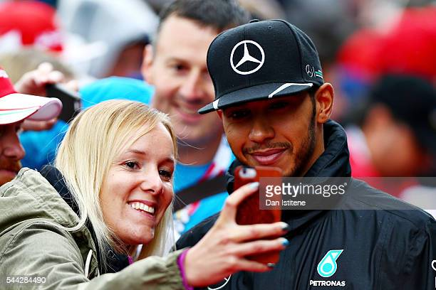 Lewis Hamilton of Great Britain and Mercedes GP arrives at the circuit and poses for a photo with a fan before the Formula One Grand Prix of Austria...