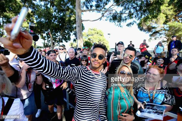 Lewis Hamilton of Great Britain and Mercedes GP arrives at the circuit and takes a selfie with a fan during previews ahead of the Australian Formula...