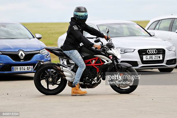 Lewis Hamilton of Great Britain and Mercedes GP arrives at the circuit on his MV Augusta Brutale motorcycle during previews ahead of the Formula One...