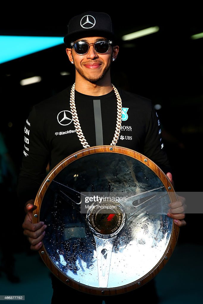 Lewis Hamilton of Great Britain and Mercedes GP celebrate with the trophy outside the team garage after the Australian Formula One Grand Prix at Albert Park on March 15, 2015 in Melbourne, Australia.
