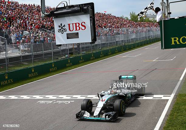 Lewis Hamilton of Great Britain and Mercedes GP celebrates as he takes the chequered flag to win the Canadian Formula One Grand Prix at Circuit...