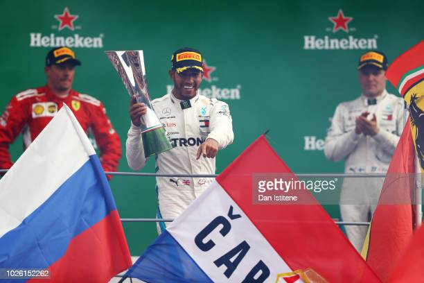 Lewis Hamilton of Great Britain and Mercedes GP celebrates his victory on the podium next to Kimi Raikkonen of Finland and Ferrari and Valtteri...