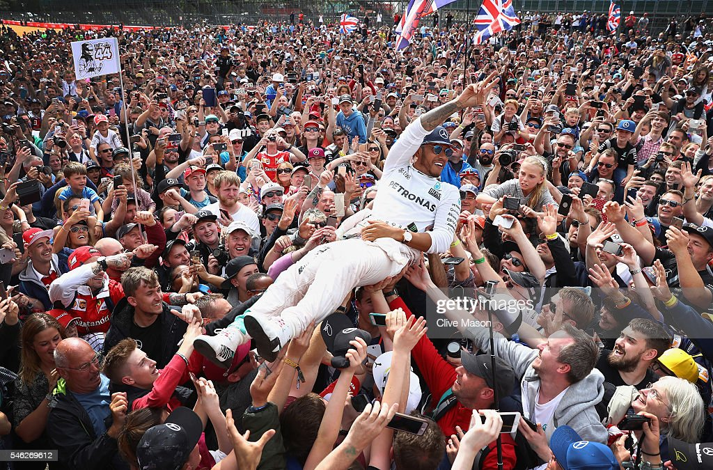 Lewis Hamilton of Great Britain and Mercedes GP celebrates his win with fans on the start finish straight after the Formula One Grand Prix of Great Britain at Silverstone on July 10, 2016 in Northampton, England.