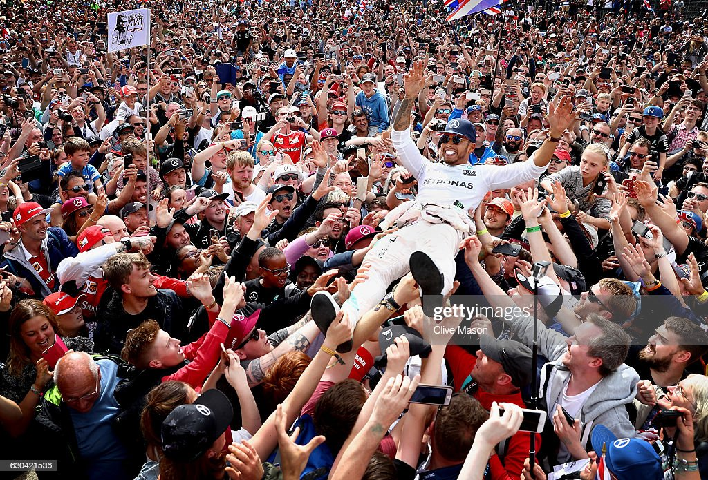 Lewis Hamilton of Great Britain and Mercedes GP celebrates his win with fans by crowd surfing on the start finish straight after the Formula One Grand Prix of Great Britain at Silverstone on July 10, 2016 in Northampton, England.
