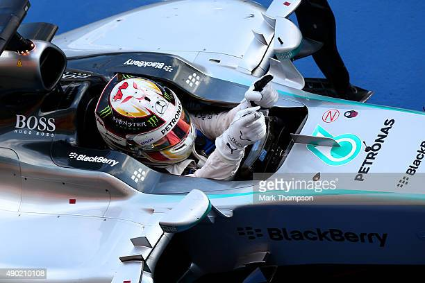 Lewis Hamilton of Great Britain and Mercedes GP celebrates in Parc Ferme after winning the Formula One Grand Prix of Japan at Suzuka Circuit on...