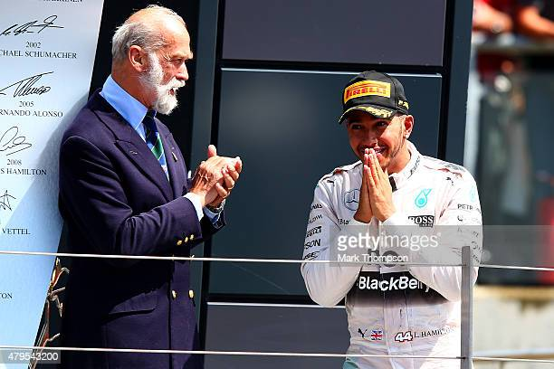 Lewis Hamilton of Great Britain and Mercedes GP celebrates next to Prince Michael of Kent on the podium after winning the Formula One Grand Prix of...