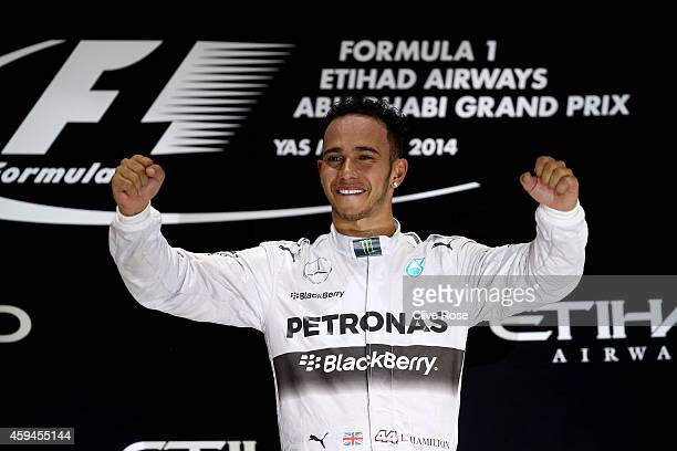 Lewis Hamilton of Great Britain and Mercedes GP celebrates on the podium after winning the World Championship and the Abu Dhabi Formula One Grand...