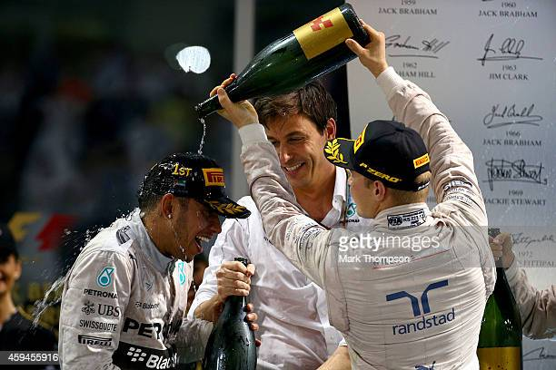 Lewis Hamilton of Great Britain and Mercedes GP celebrates on the podium with Mercedes GP Executive Director Toto Wolff and Valtteri Bottas of...