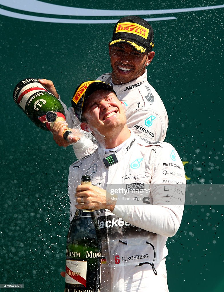 Lewis Hamilton of Great Britain and Mercedes GP celebrates on the podium next to Nico Rosberg of Germany and Mercedes GP after winning the Formula One Grand Prix of Great Britain at Silverstone Circuit on July 5, 2015 in Northampton, England.