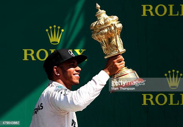 Lewis Hamilton of Great Britain and Mercedes GP celebrates on the podium after winning the Formula One Grand Prix of Great Britain at Silverstone...