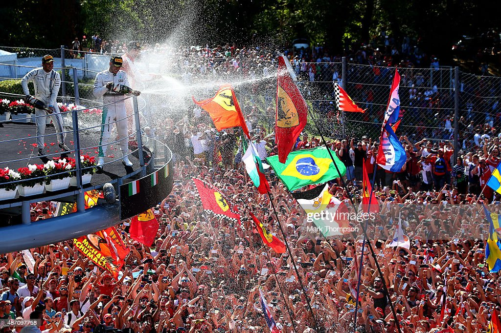 Lewis Hamilton of Great Britain and Mercedes GP celebrates on the podium next to Sebastian Vettel of Germany and Ferrari and Felipe Massa of Brazil and Williams after winning the Formula One Grand Prix of Italy at Autodromo di Monza on September 6, 2015 in Monza, Italy.