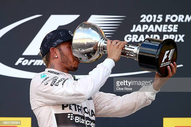 Lewis Hamilton of Great Britain and Mercedes GP celebrates on the podium with the trophy after winning the Formula One Grand Prix of Japan at Suzuka...