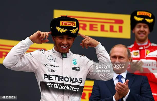 Lewis Hamilton of Great Britain and Mercedes GP celebrates on the podium next to President of Russia Vladimir Putin and Sebastian Vettel of Germany...