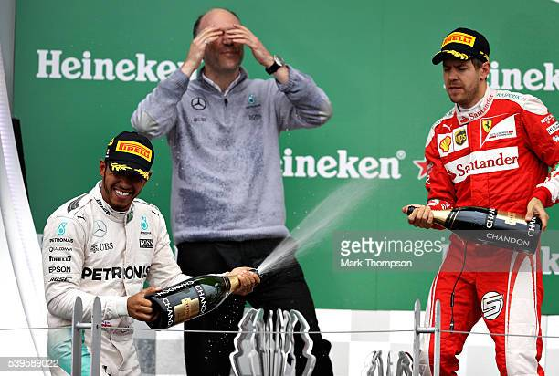 Lewis Hamilton of Great Britain and Mercedes GP celebrates on the podium with Sebastian Vettel of Germany and Ferrari during the Canadian Formula One...