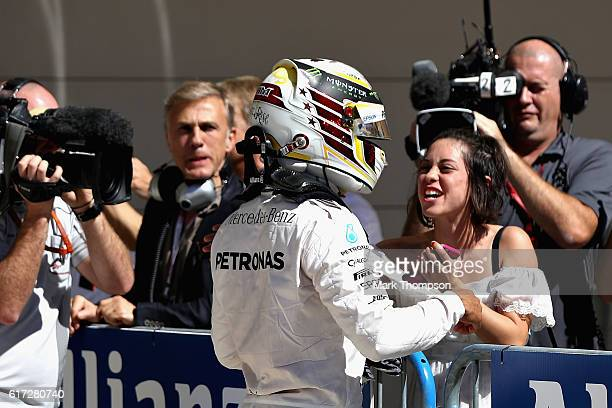 Lewis Hamilton of Great Britain and Mercedes GP celebrates qualifying in pole position with actor Rosa Salazer in parc ferme during qualifying for...