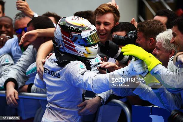 Lewis Hamilton of Great Britain and Mercedes GP celebrates victory with team mates and mechanics in parc ferme after the Malaysia Formula One Grand...