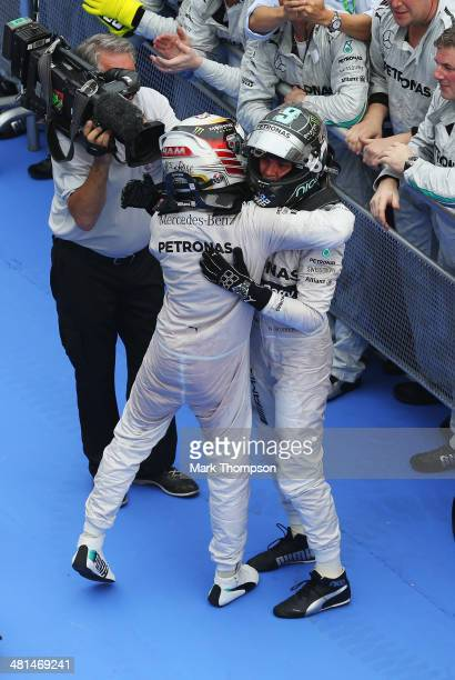 Lewis Hamilton of Great Britain and Mercedes GP celebrates victory with team mate and second placed Nico Rosberg of Germany and Mercedes GP in parc...