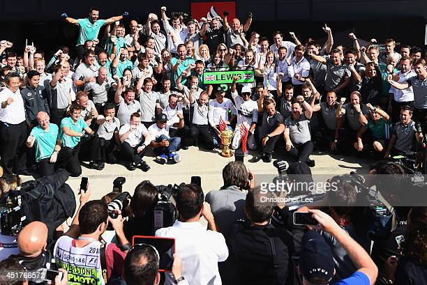 Lewis Hamilton of Great Britain and Mercedes GP celebrates with his team including Nico Rosberg of Germany and Mercedes GP following his victory in...