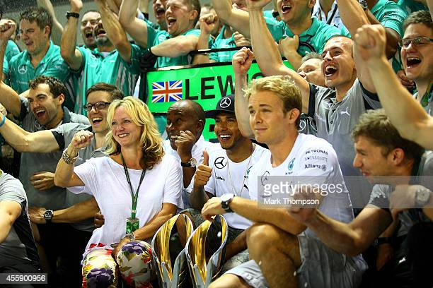 Lewis Hamilton of Great Britain and Mercedes GP celebrates with his team including Nico Rosberg of Germany and Mercedes GP his father Anthony...
