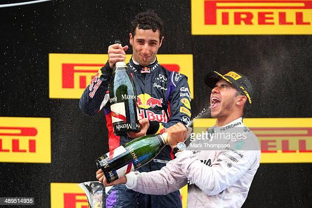 Lewis Hamilton of Great Britain and Mercedes GP celebrates with champagne on the podium next to Daniel Ricciardo of Australia and Infiniti Red Bull...