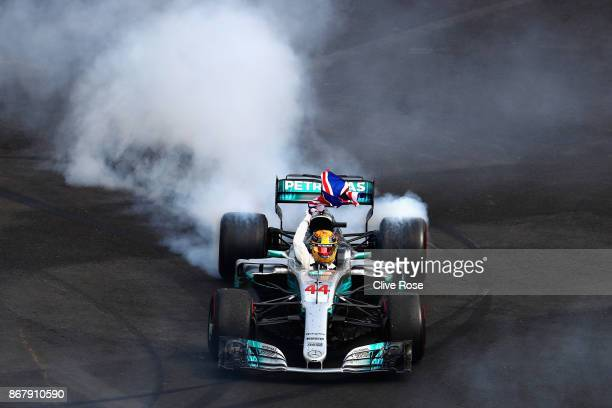 Lewis Hamilton of Great Britain and Mercedes GP celebrates with donuts on track after winning his fourth F1 World Drivers Championship during the...