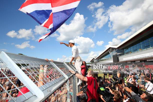 Lewis Hamilton of Great Britain and Mercedes GP celebrates with the fans after his victory in the British Formula One Grand Prix at Silverstone...