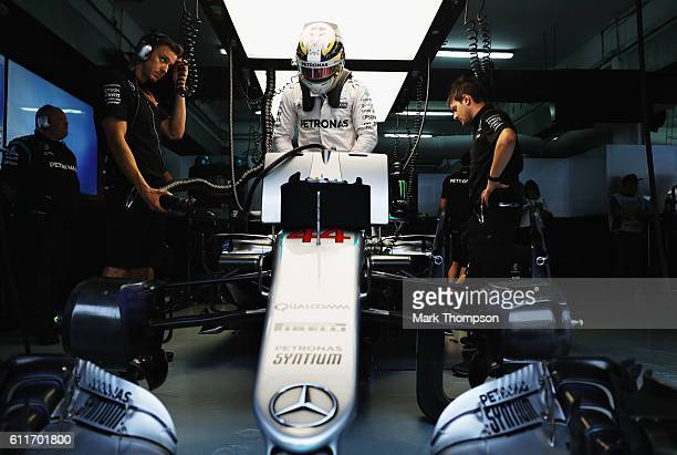 Lewis Hamilton of Great Britain and Mercedes GP climbs into his car in the garage during qualifying for the Malaysia Formula One Grand Prix at Sepang...