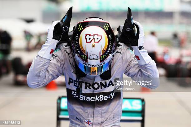 Lewis Hamilton of Great Britain and Mercedes GP climbs out of his car in victory at parc ferme after the Malaysia Formula One Grand Prix at the...