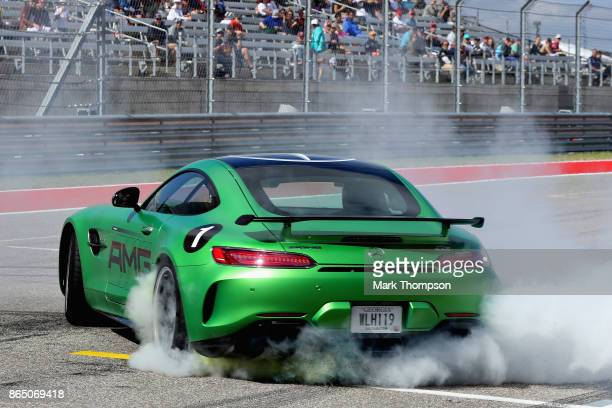 Lewis Hamilton of Great Britain and Mercedes GP does donuts on track with sprinting legend Usain Bolt as a passenger before the United States Formula...