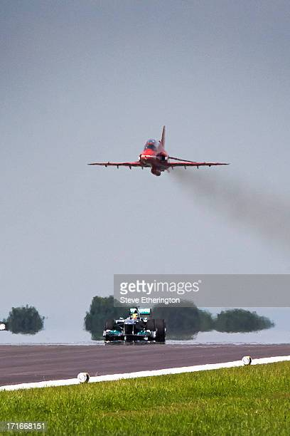 Lewis Hamilton of Great Britain and Mercedes GP drives his car along the runway beneath a RAF Hawk as he takes part in a training and flying session...