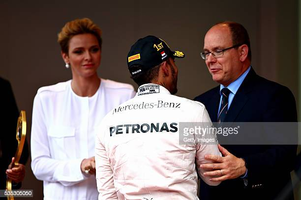 Lewis Hamilton of Great Britain and Mercedes GP is congratulated by Prince Albert of Monaco on the podium during the Monaco Formula One Grand Prix at...