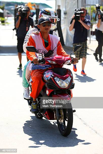 Lewis Hamilton of Great Britain and Mercedes GP is driven back to the paddock on the back of a scooter during practice for the Malaysia Formula One...