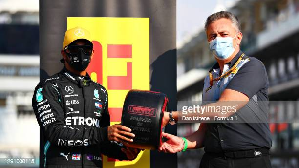 Lewis Hamilton of Great Britain and Mercedes GP is presented with the Pirelli Poleman of the Year award by Director of Pirelli F1 Mario Isola prior...